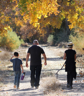 Family walking through Valle de Oro Paseo del Bosque Trail